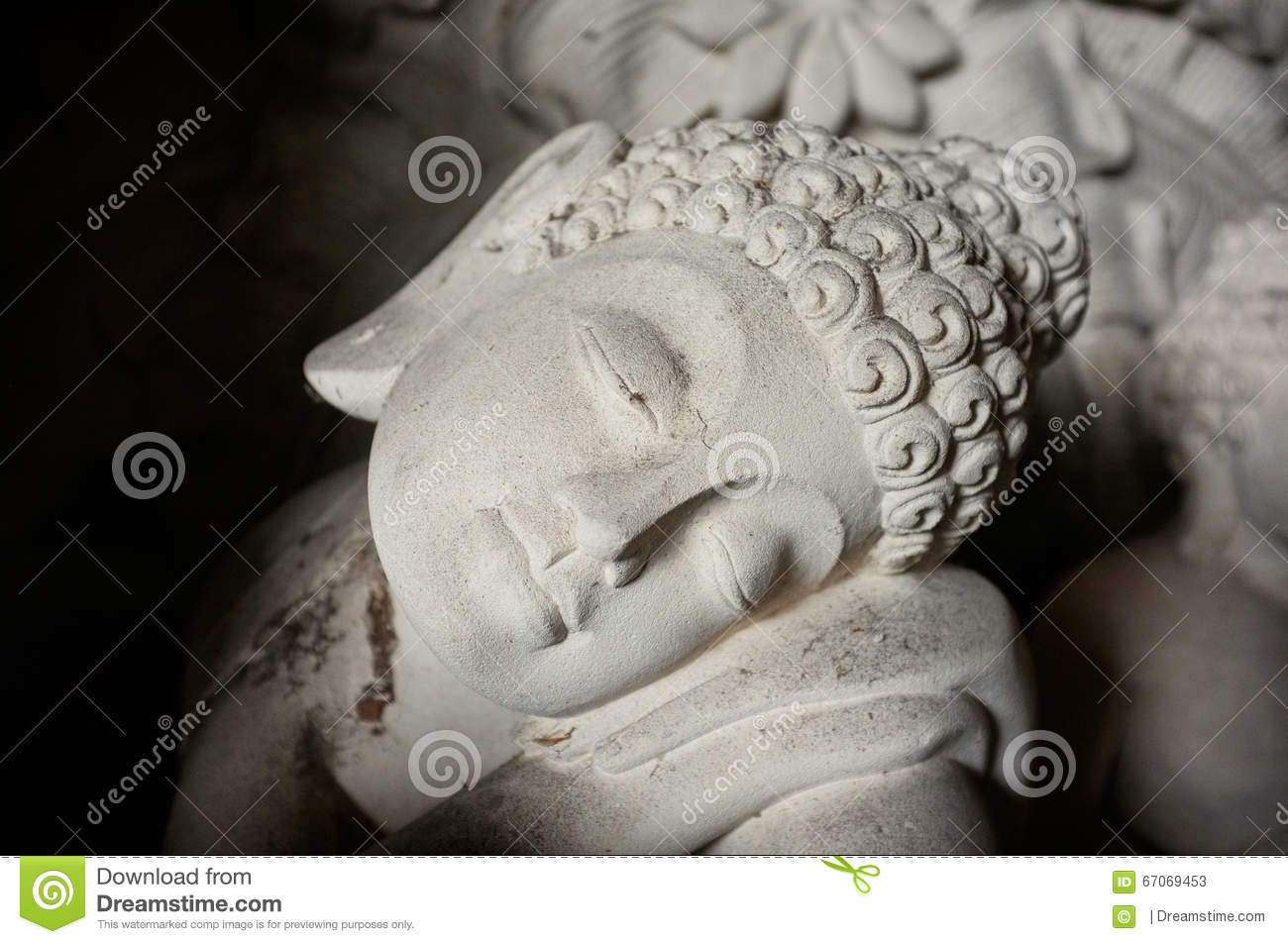 A hand carved stone statue of reclining buddha in ubud
