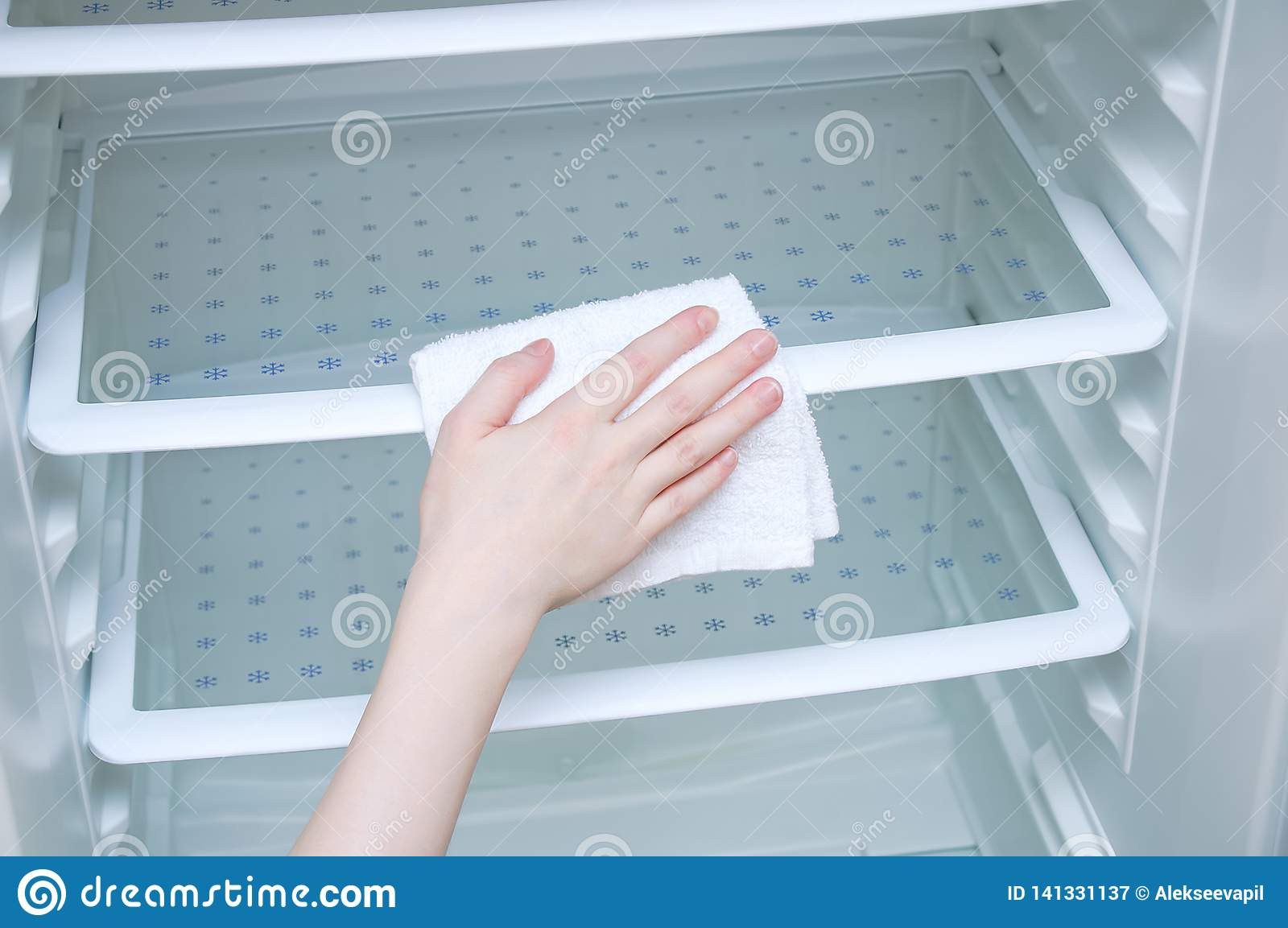 Hand caucasian girl with a white rag washes the fridge.