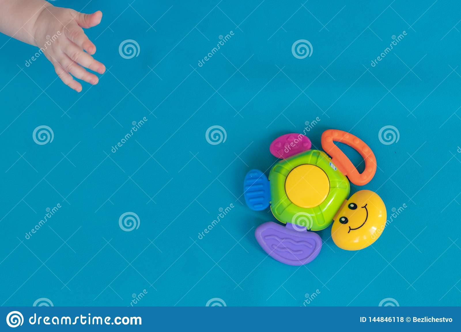 The hand of the child reaches for a multicolored toy turtle, which hovering against a blue background. Diagonal. Close-up