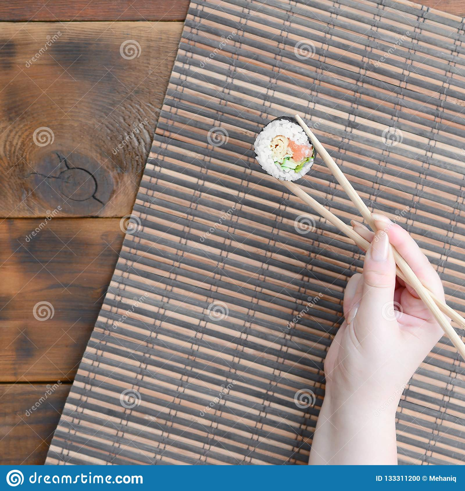 A hand with chopsticks holds a sushi roll on a bamboo straw serwing mat background. Traditional Asian food
