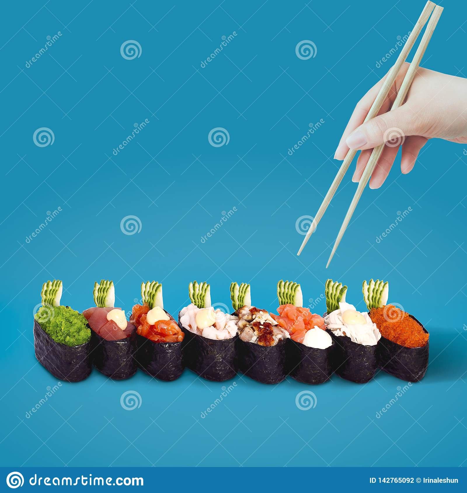 Hand with chopsticks selects sushi on a blue background.