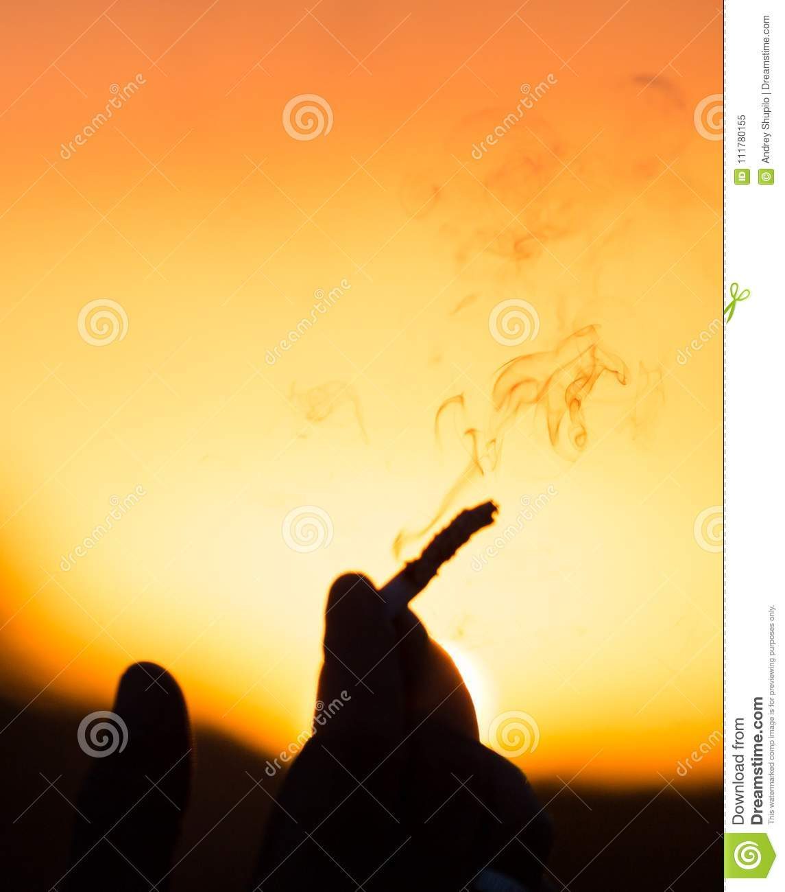 Hand with a cigarette at sunset