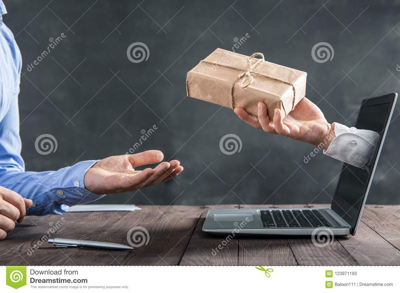 Hand coming out of the laptop gives the package