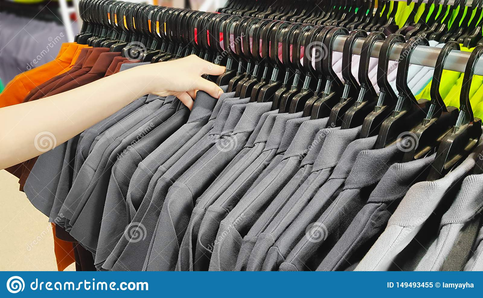 Hand of Customer Choosing Discount Clothes in a Shopping Mall. People Searching or Buying Cheap Cotton Gray T-Shirt on Rack Hanger
