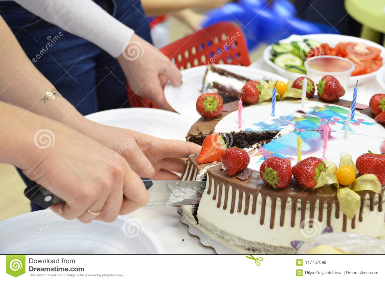 Hand Cut The Birthday Cake With KnifeBirthday Inscription Congratulations A Table Full Of