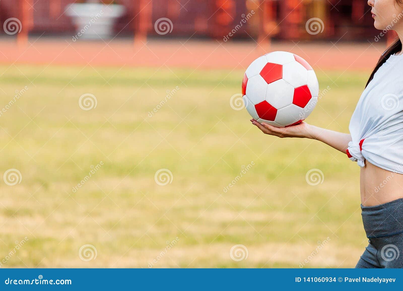 In hand de bal van het voetbal Close-up De ruimte van het exemplaar Het concept van het voetbalspel
