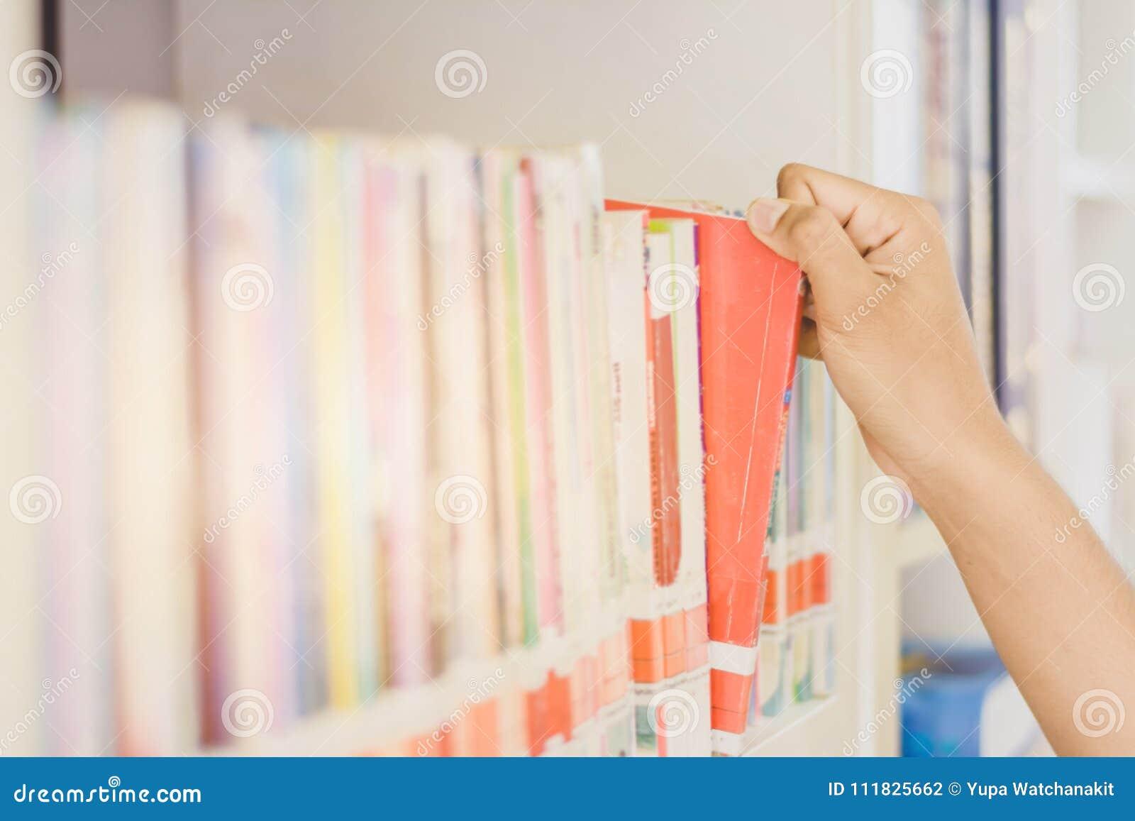Hand des asiatischen Studenten ein Buch für das Ablesen in College libr auswählend