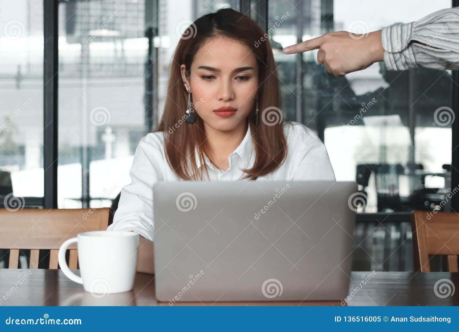 Hand des verärgerten Chefs besorgte betonte asiatische Geschäftsfrau im Büro zeigend