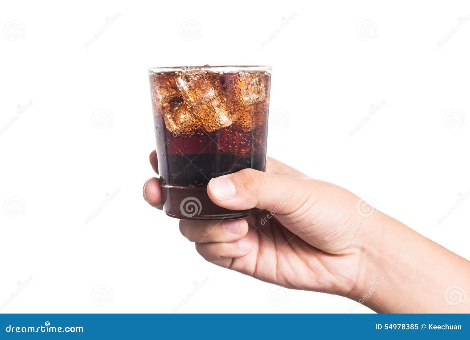 Hand die een glas van ijs gevulde koude en bruisende koladrank houden