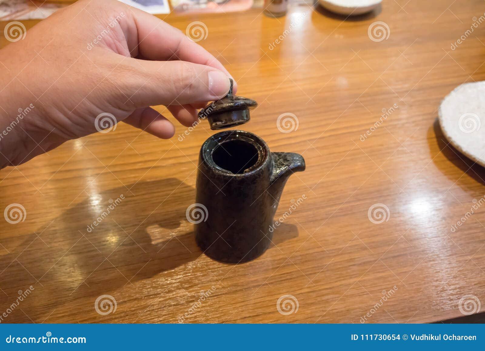 Hand die een Japanse sojasaus ceramische theepot met deksel houden