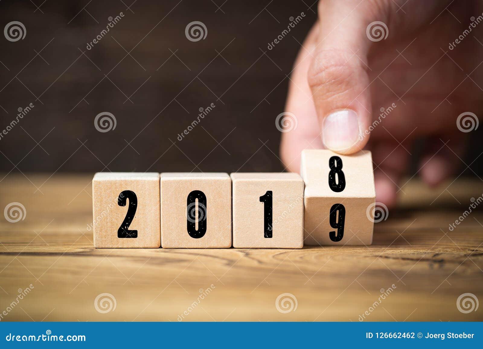 Hand die een kubus wegknippen, symbolizng de verandering vanaf 2018 tot 2019
