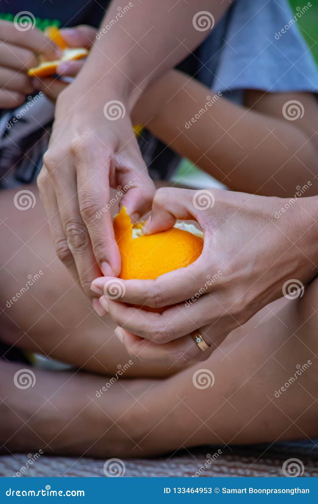 Hand die een sinaasappel en een schil houden