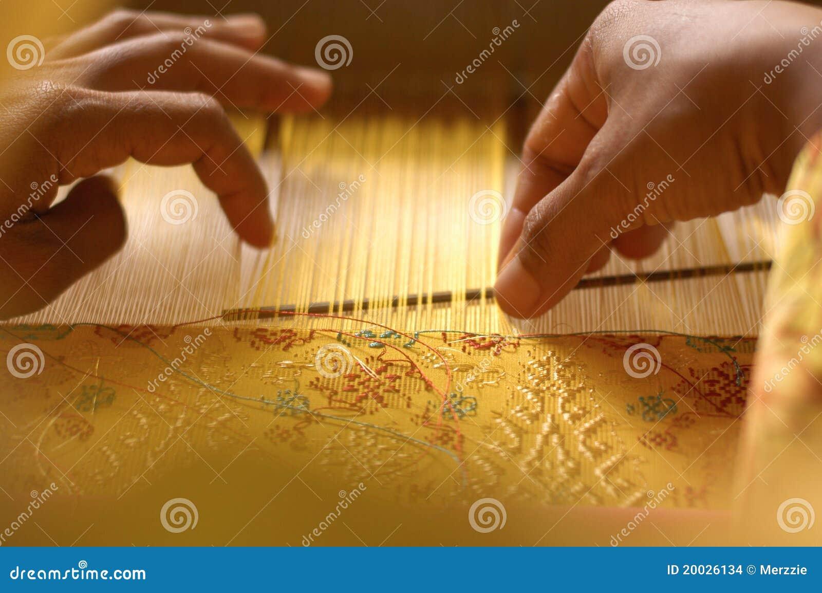 Hand, die ein Songket spinnt