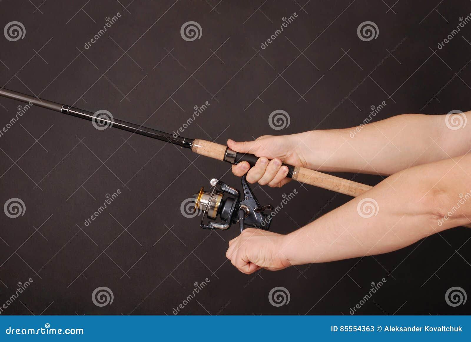 Hand, die eine Angelrute hält
