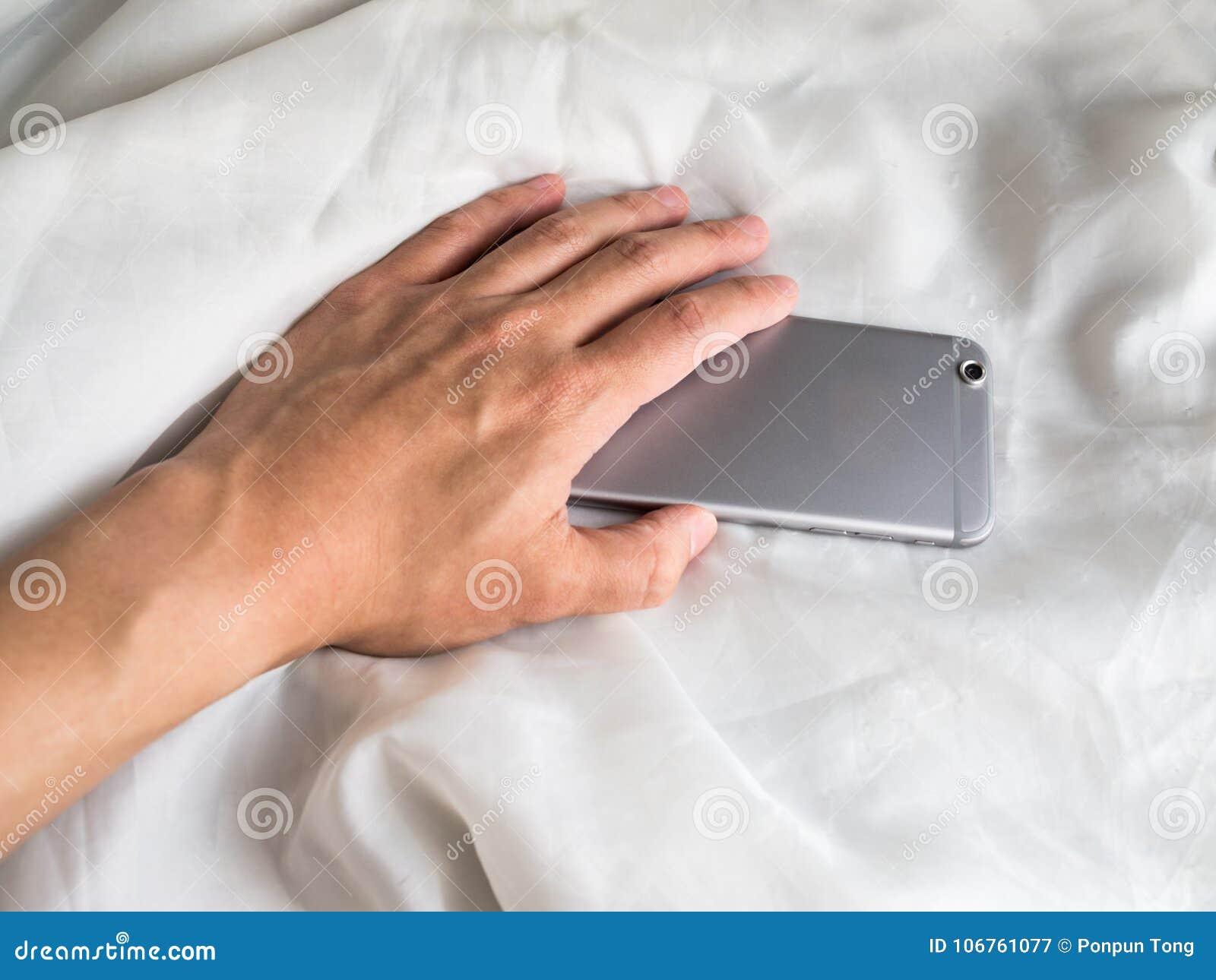 Hand, die für Telefon im Bett erreicht