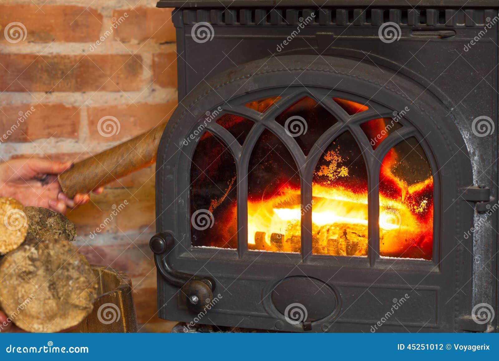 Hand die hout op brandopen haard zetten heating