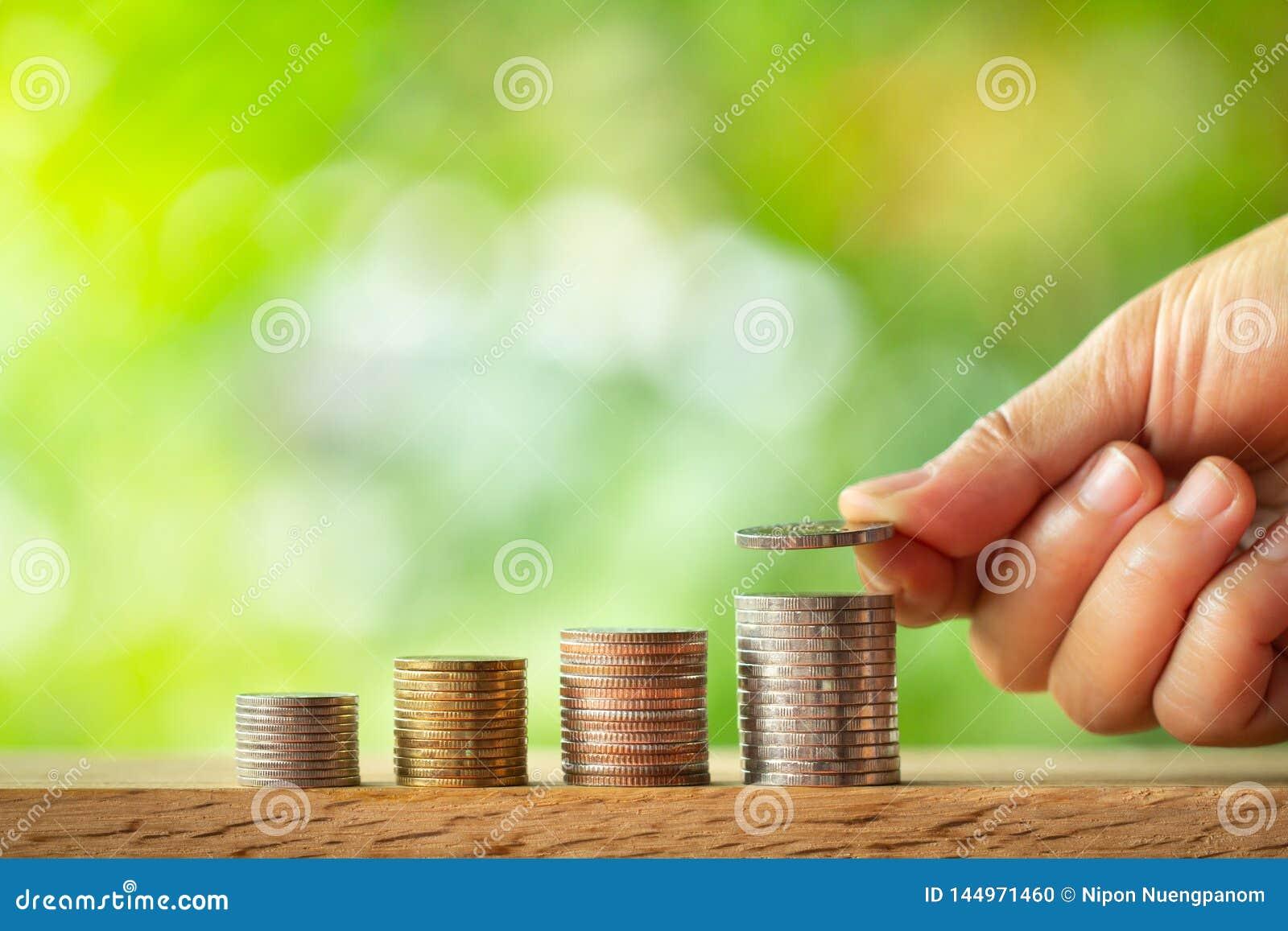 Hand die muntstuk op muntstukkenstapel zet met groen vage achtergrond