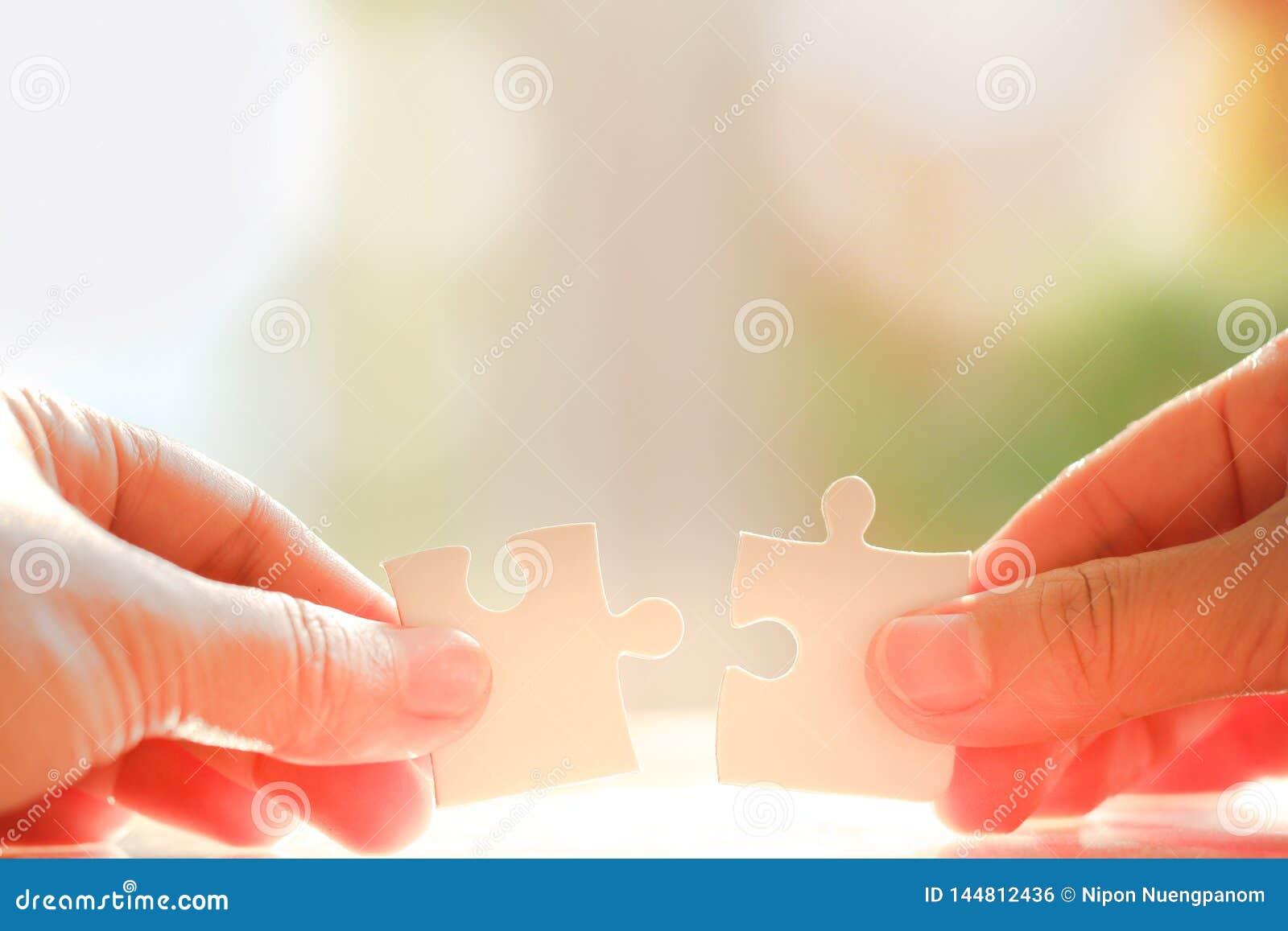 Hand, die Puzzlen h?lt und anschlie?t