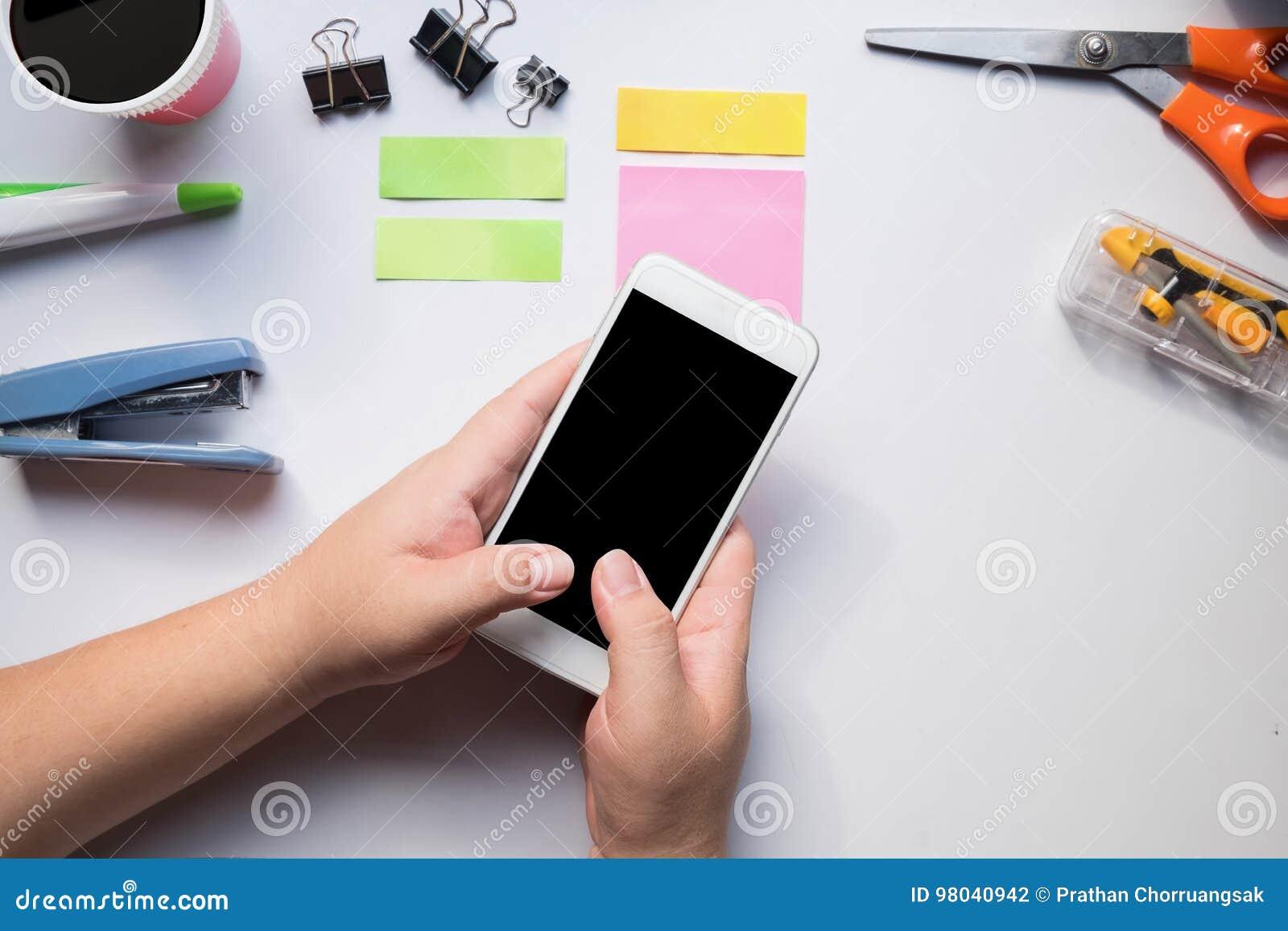 Hand die smartphone op bureau gebruikt