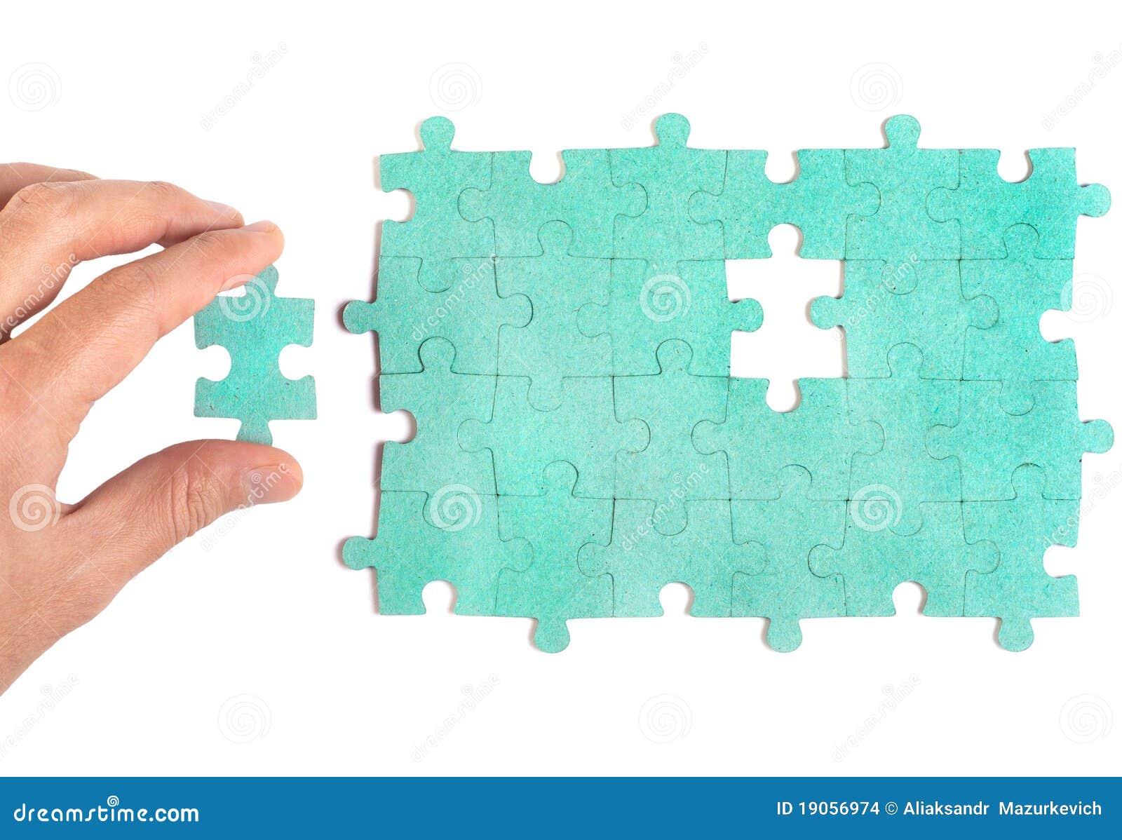 Hand die stuk van groene figuurzaag opneemt puzzlel