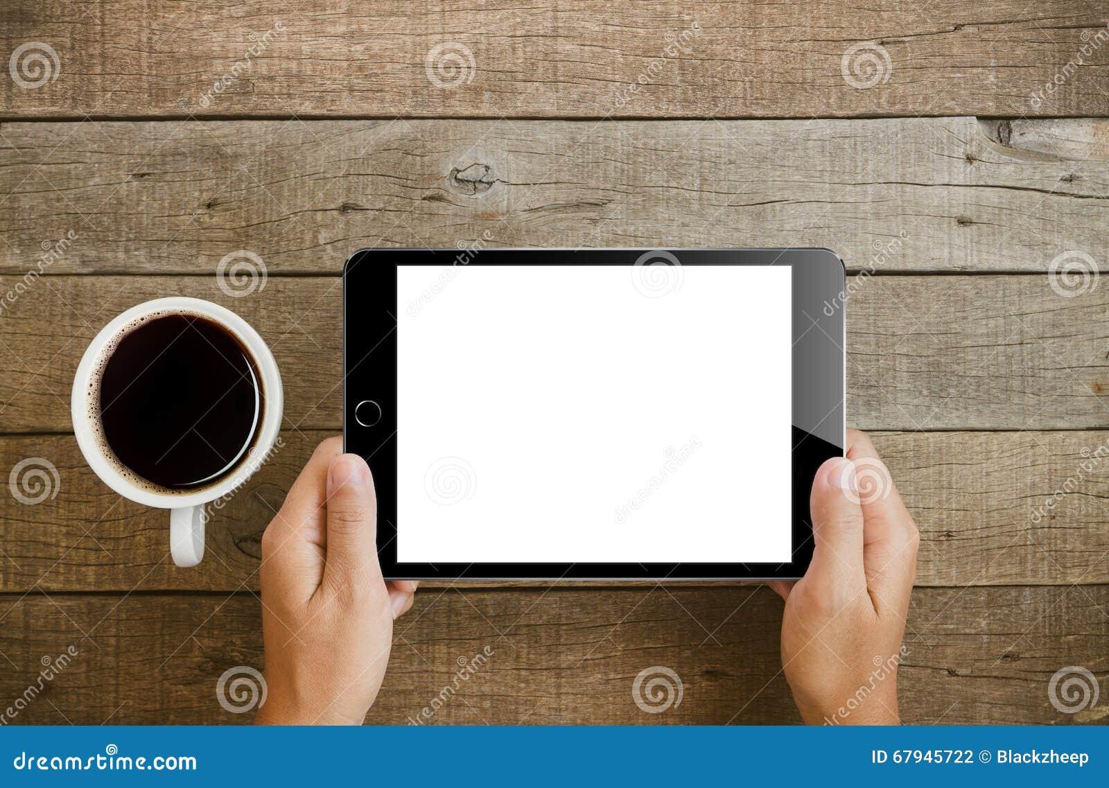 Hand, die Tablette auf hölzerner Tabelle hält