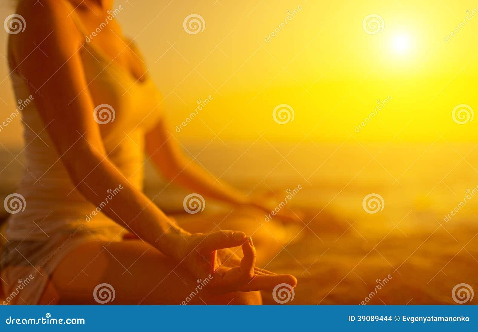 Hand die van vrouw in yoga de mediteren stelt op strand