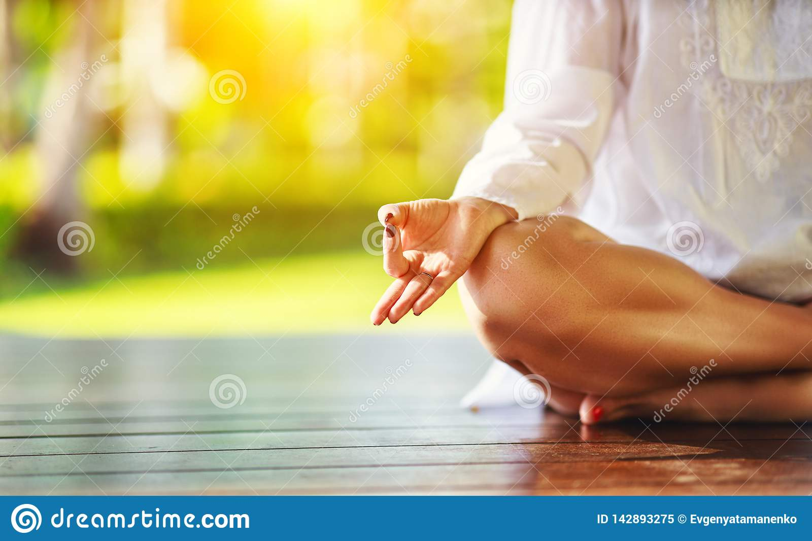 Hand die van vrouw yoga op de aard in park doen