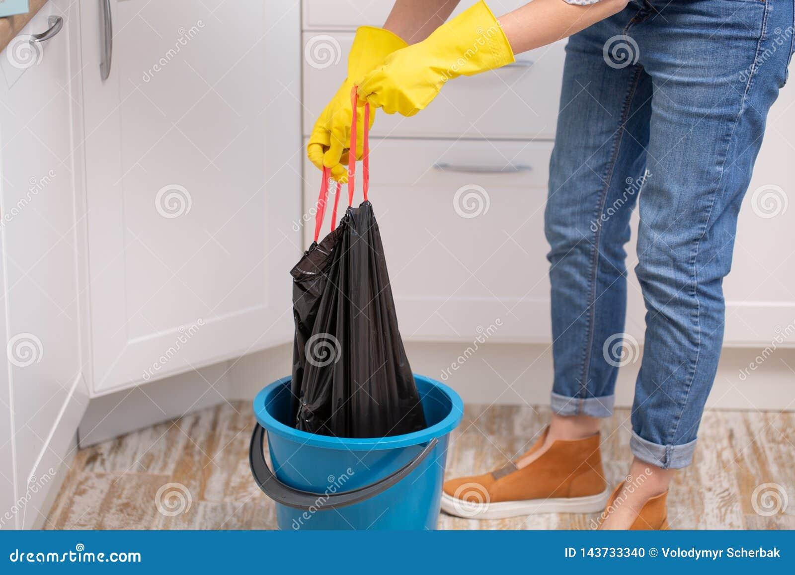 Hand, die zu Hause eine Abfallabfalltasche hält, um sie wegzunehmen