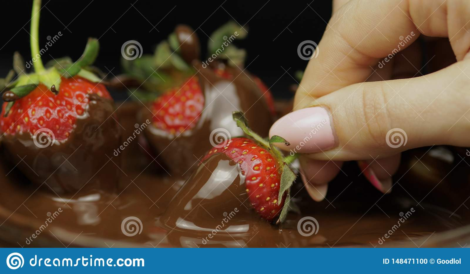 Hand dipping strawberry in melted chocolate. Fresh berries sweet dessert food