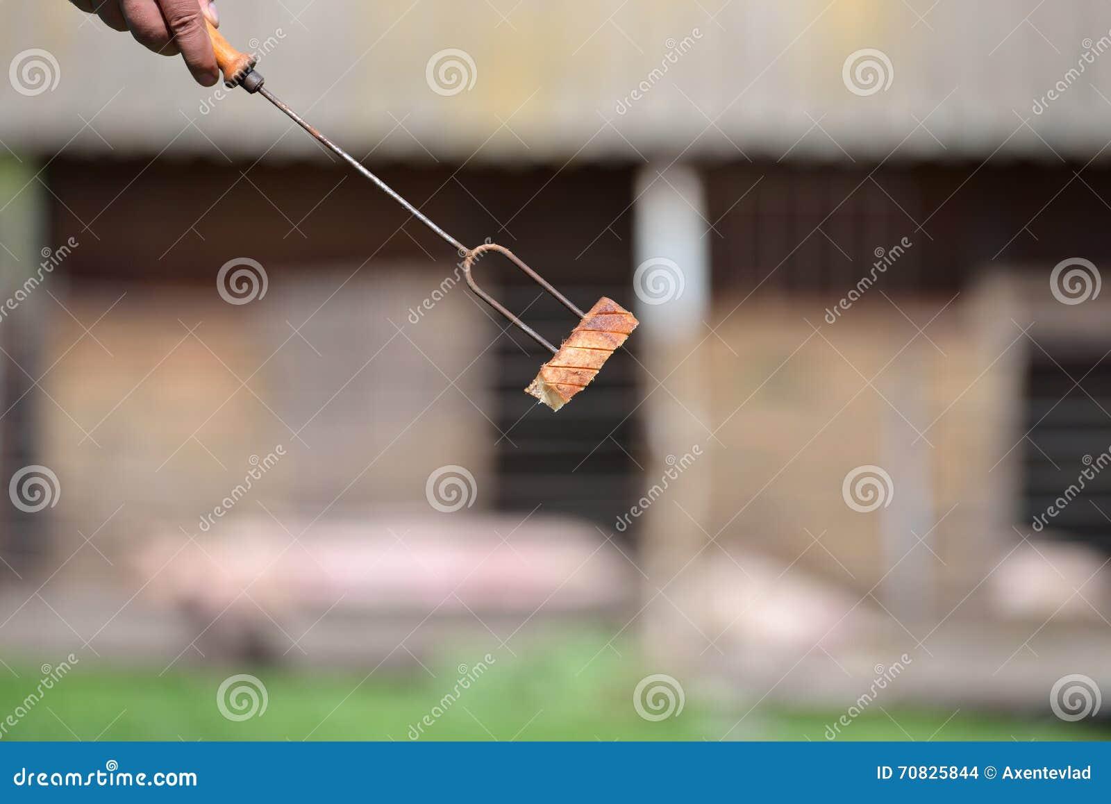 Hand einer Person, die eine Gabel mit einer Scheibe des Speckes für Stange hält