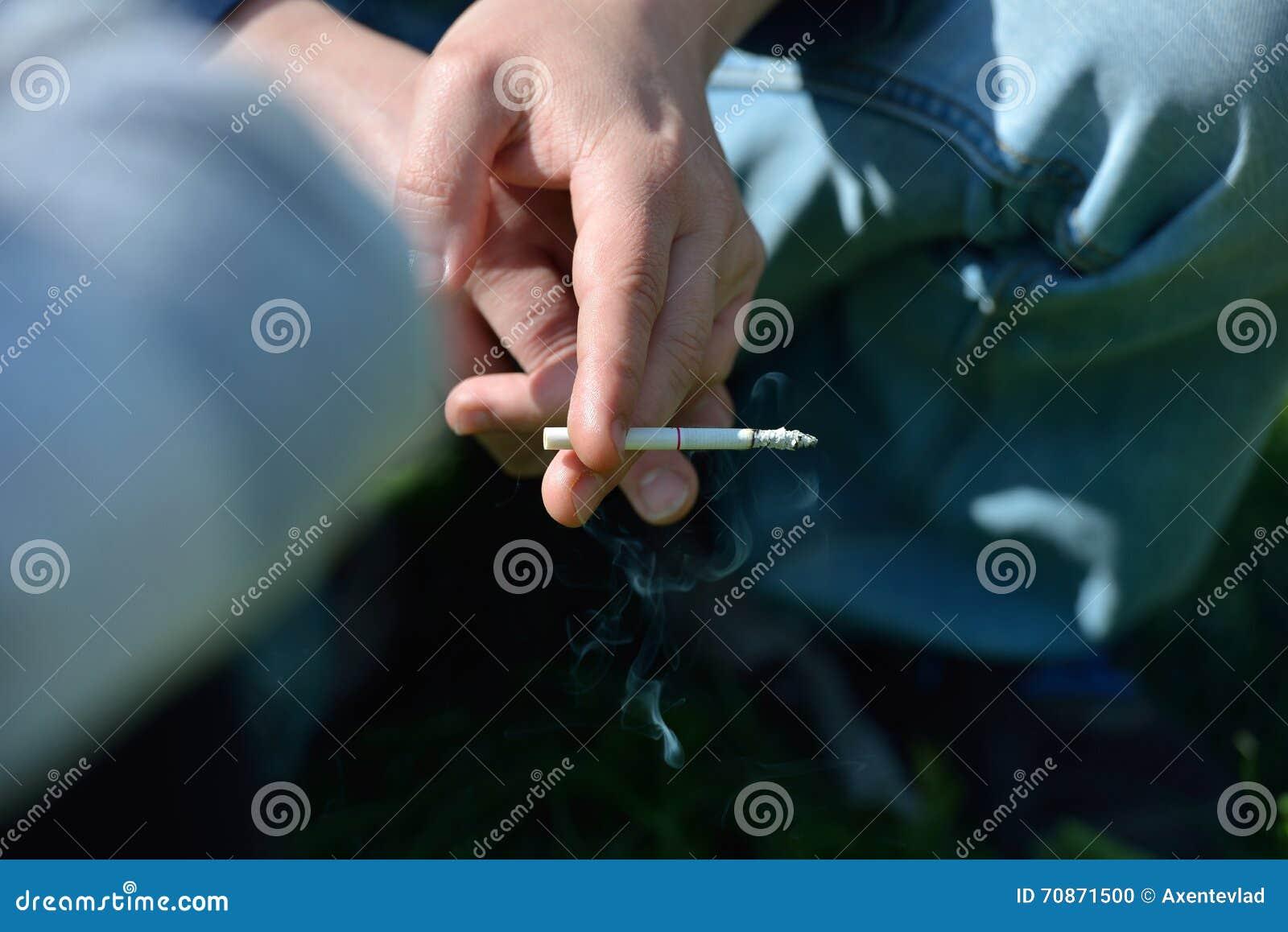 Hand eines Mannes, der in der Hand eine Zigarette draußen, auf einem backgrou hält