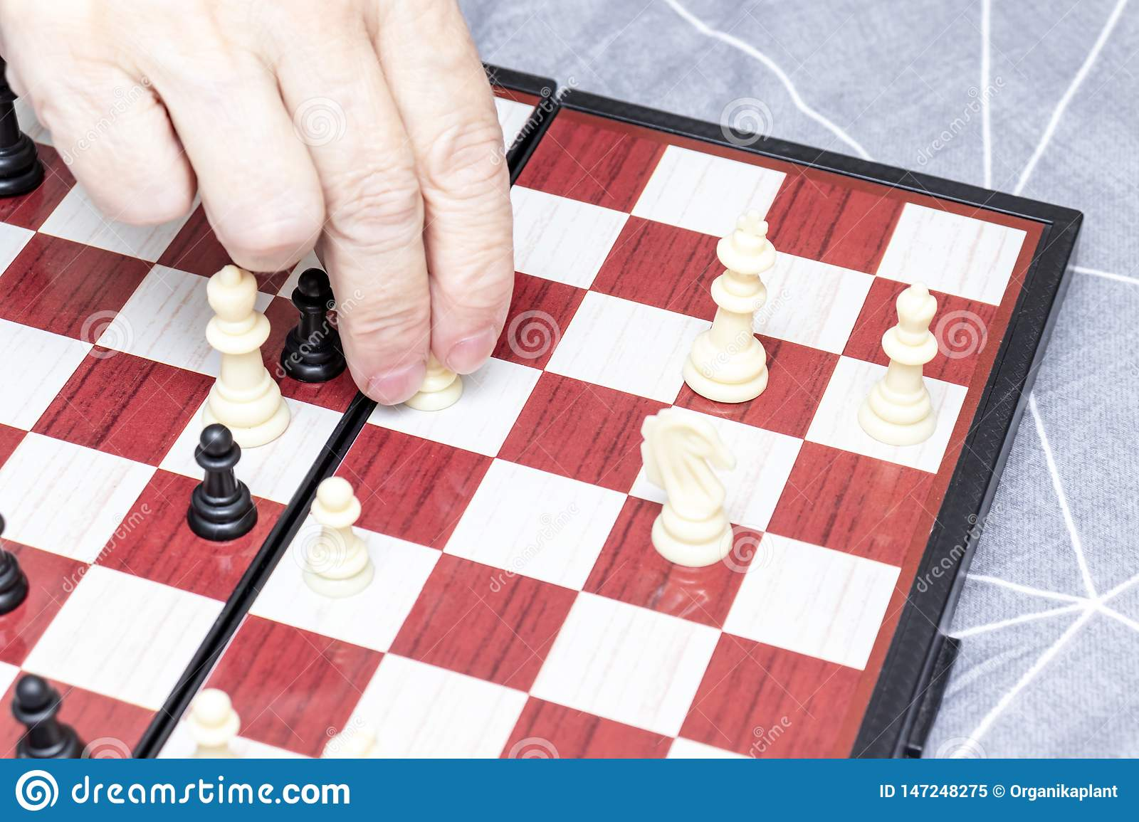 Hand of an elderly senior woman playing chess close up, entertainment and intellectual activity for retired people concept