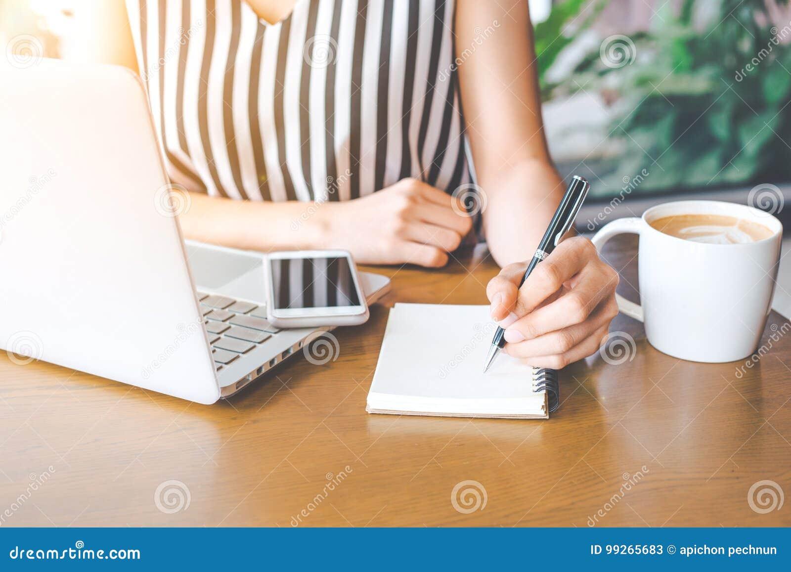 Hand för affärskvinna som arbetar på en dator och skriver på noteped med en penna