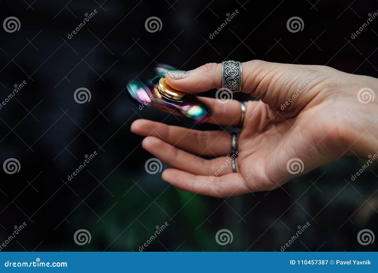 Hand för flicka` s med rastlös människaspinnaren Rymmer en skinande metallisk handspinnare Hippier och Bohemia