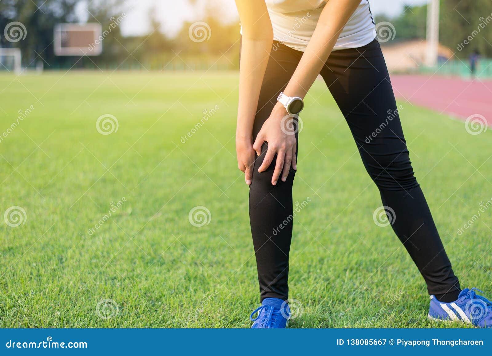 Hand för friidrottkvinnalöpare som trycker på och har ett knä att smärta och skada, når att ha kört som är utomhus-
