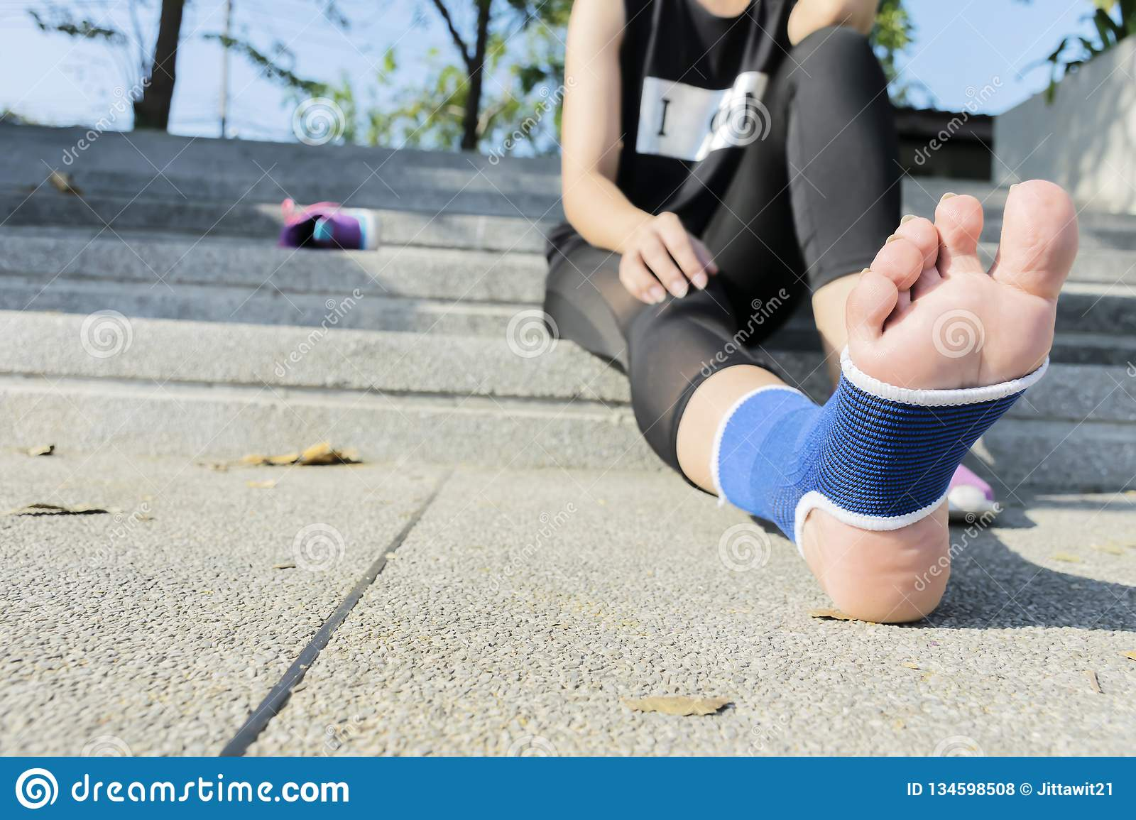 Hand female using elastic bandage with legs,Female putting bandage on her injured foot from sport