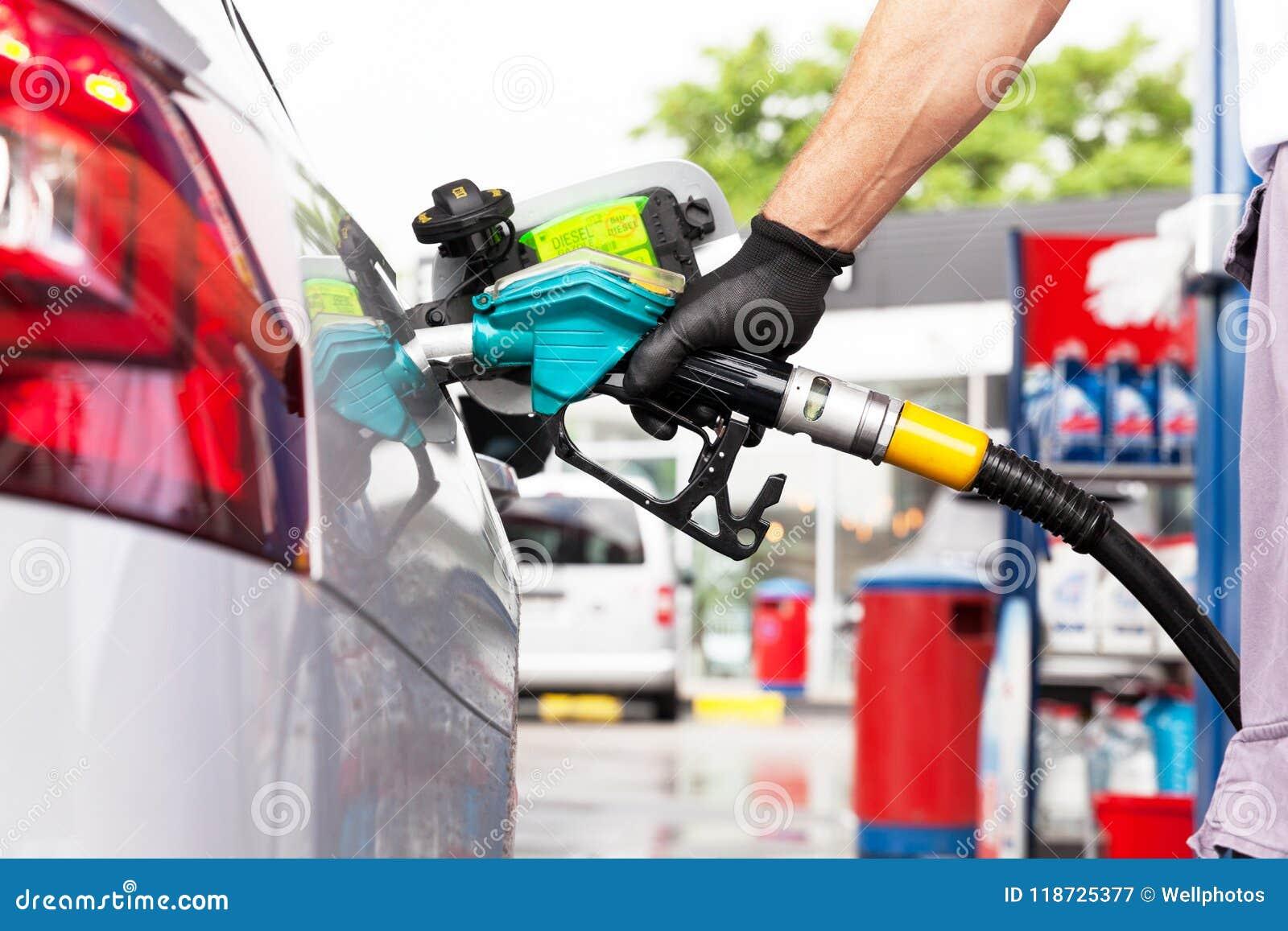 Man filling diesel fuel in car at gas station