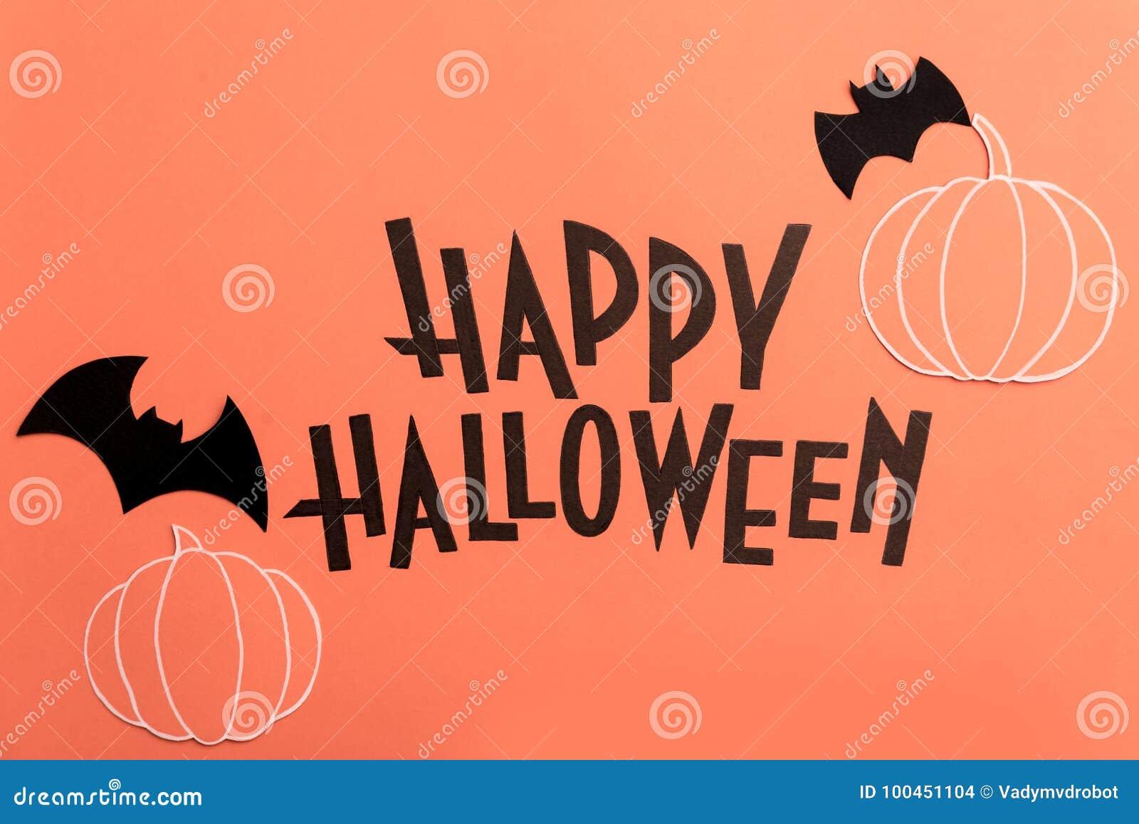 Hand geschreven uitdrukking Gelukkig Halloween met pompoenen en knuppels dichtbij het