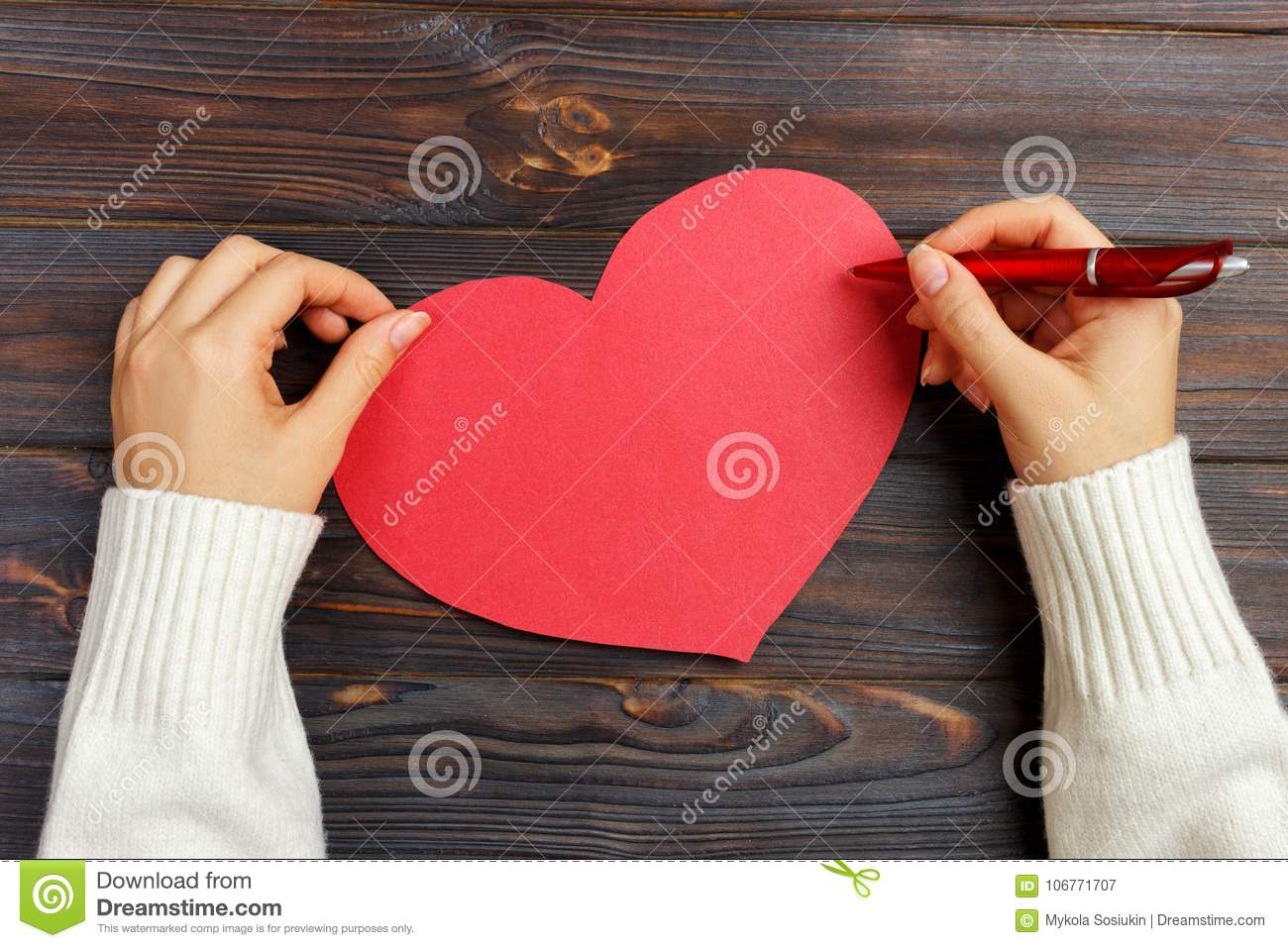 Hand of girl writing love letter on Valentine Day. Handmade red heart postcard. Woman write on postcard for 14 February holiday ce