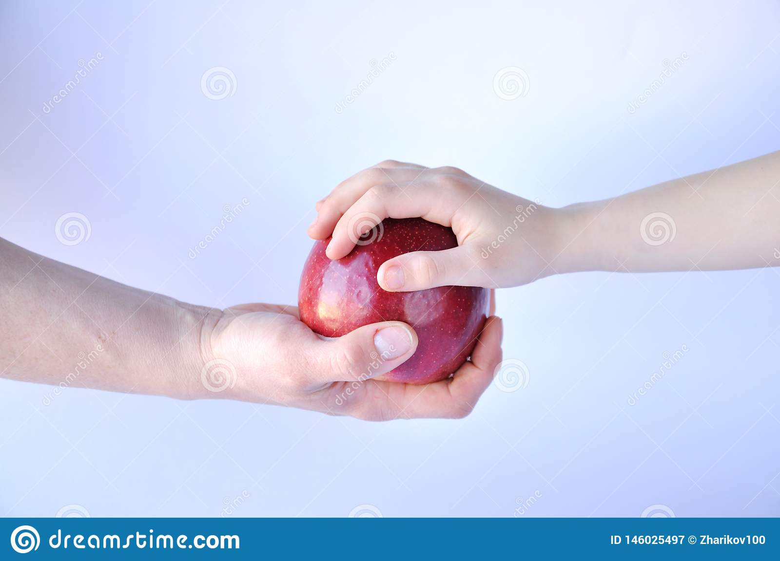 Hand gives a red apple to another hand