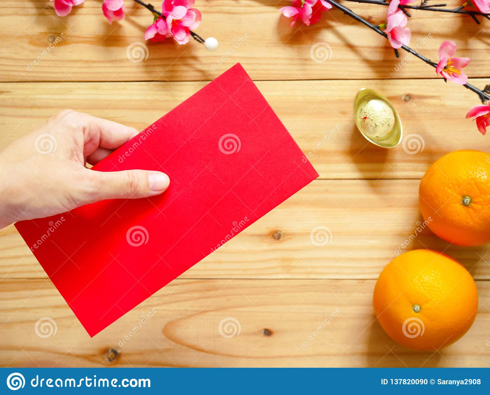 Hand Giving Red Packet Over Chinese New Year Decorations ...