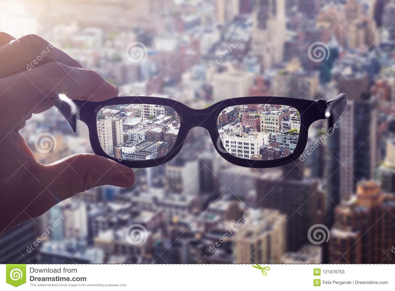 331a6bd2ec Cityscape focused in glasses lenses with hand holding the eyewear between  thumb and index finger