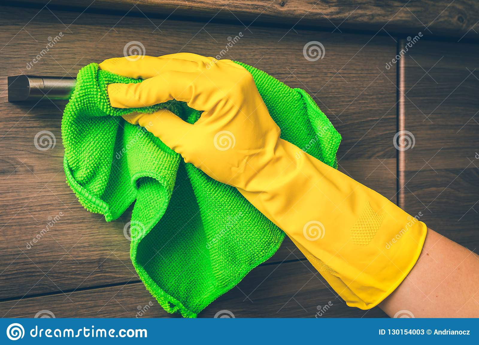 4917a8897c81a Hand in glove with green rag is cleaning stainless steel handles -  housework and housekeeping concept - retro style