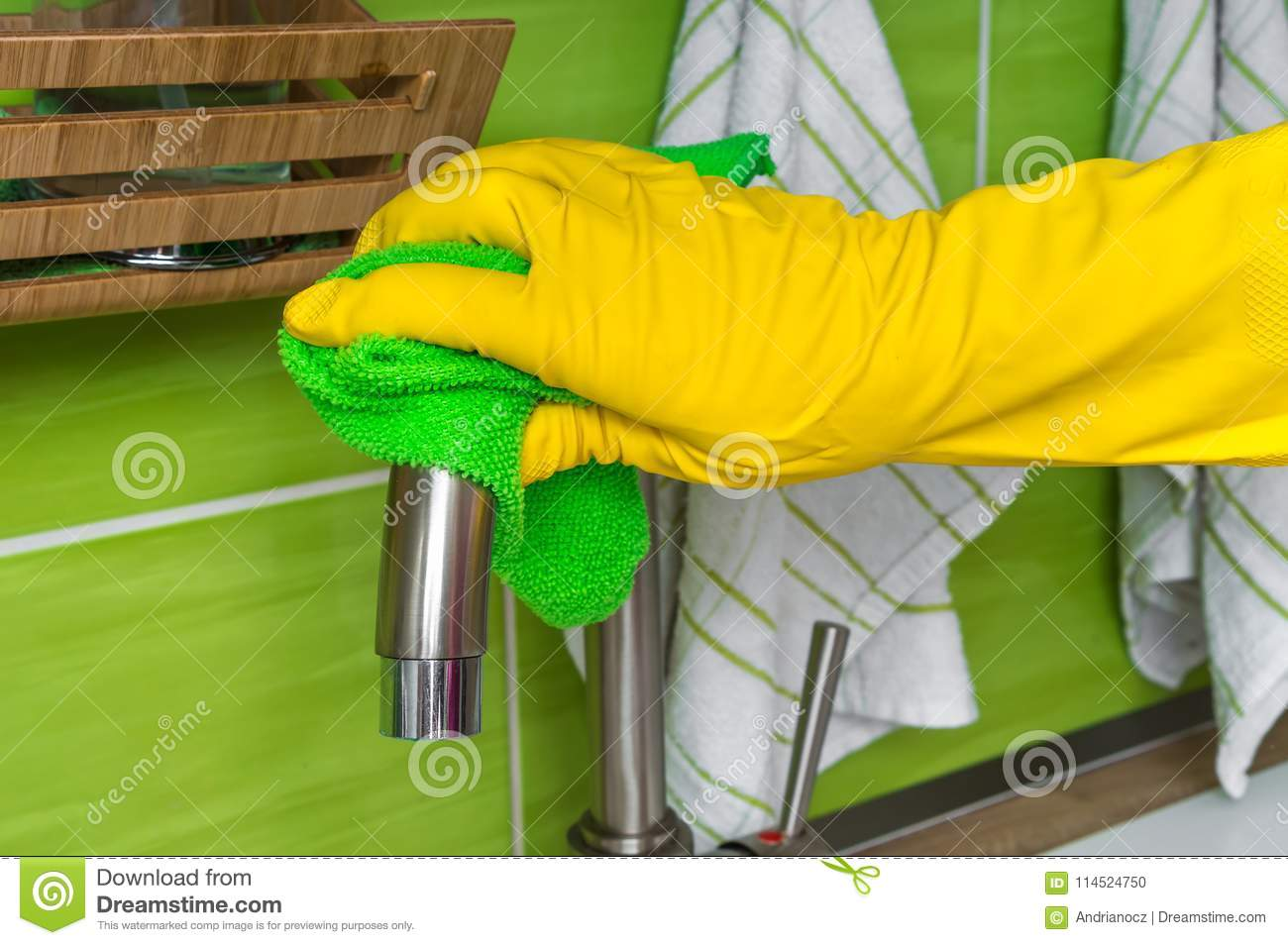 9dc435205009b Hand in glove with green rag is wiping faucet in kitchen - housework and housekeeping  concept