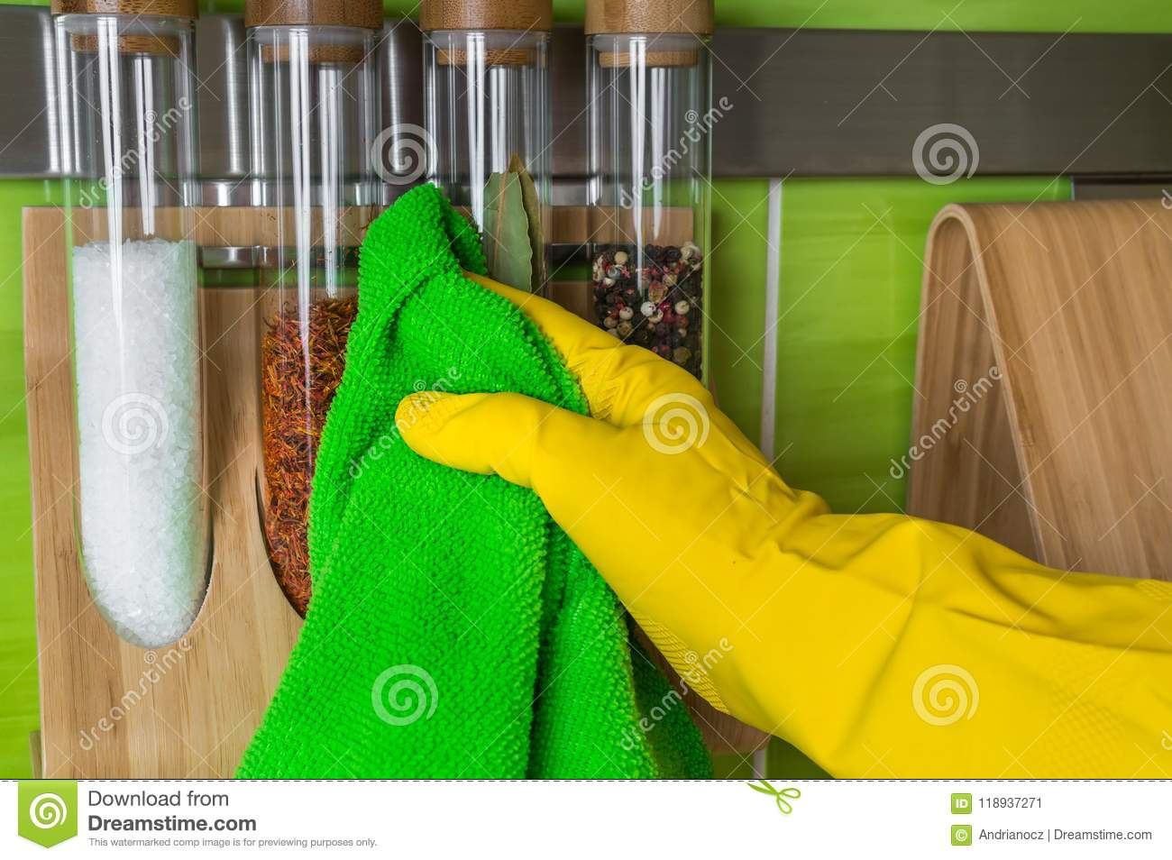 037c232d1dcdb Hand in glove with green rag is wiping spice bottles - housework and housekeeping  concept