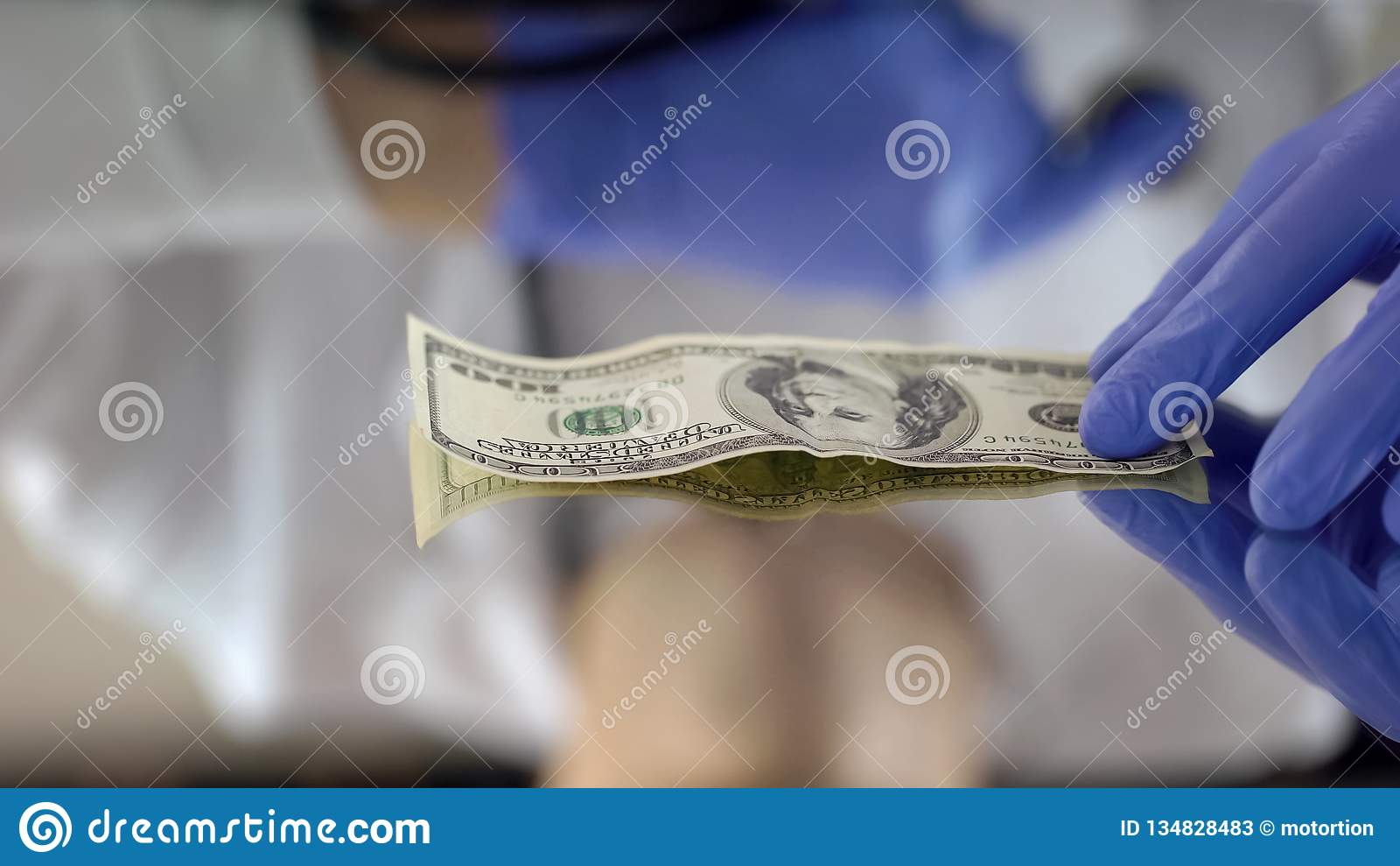 Hand in glove holding dollar banknote, expert checking suspicious money, fake
