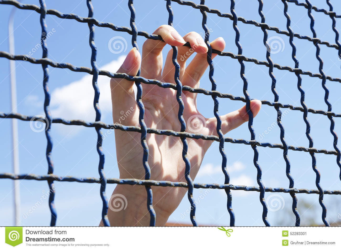Hand Grasping A Metal Fence Stock Photo