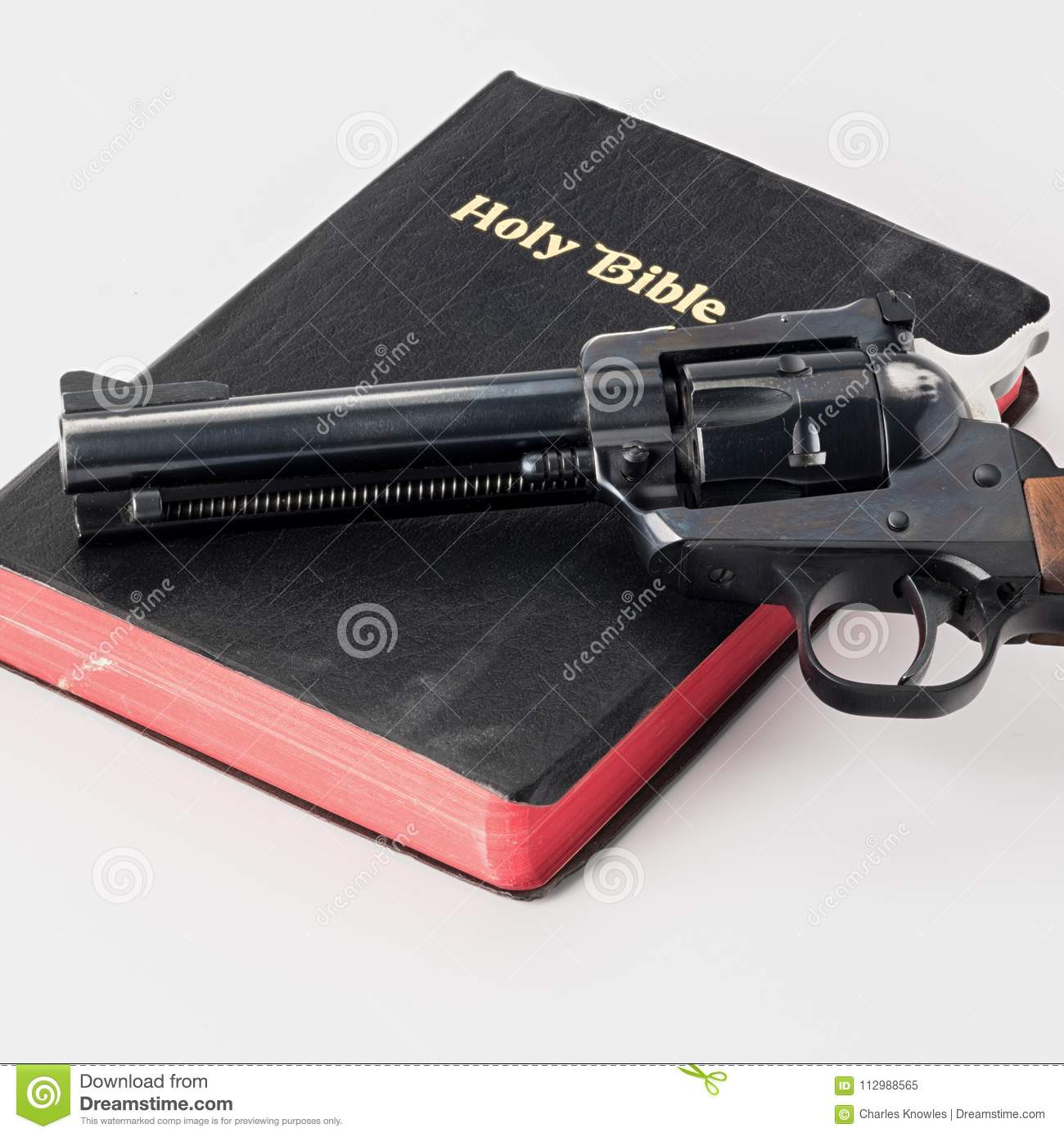 Hand gun on the top of an old Bible with red pages