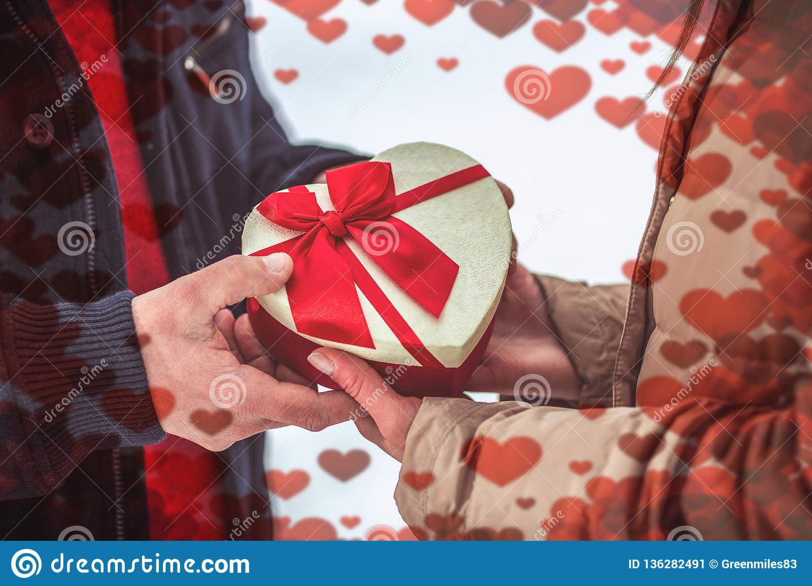 Hand of guy giving his girlfriend valentines present