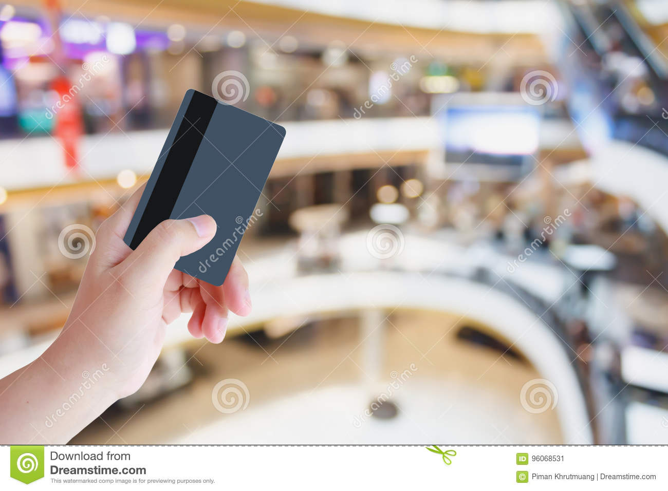 Hand hold credit card with shopping mall